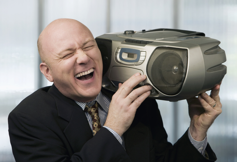 bald_man_listening_to_music_in_boom_box_at_the_office